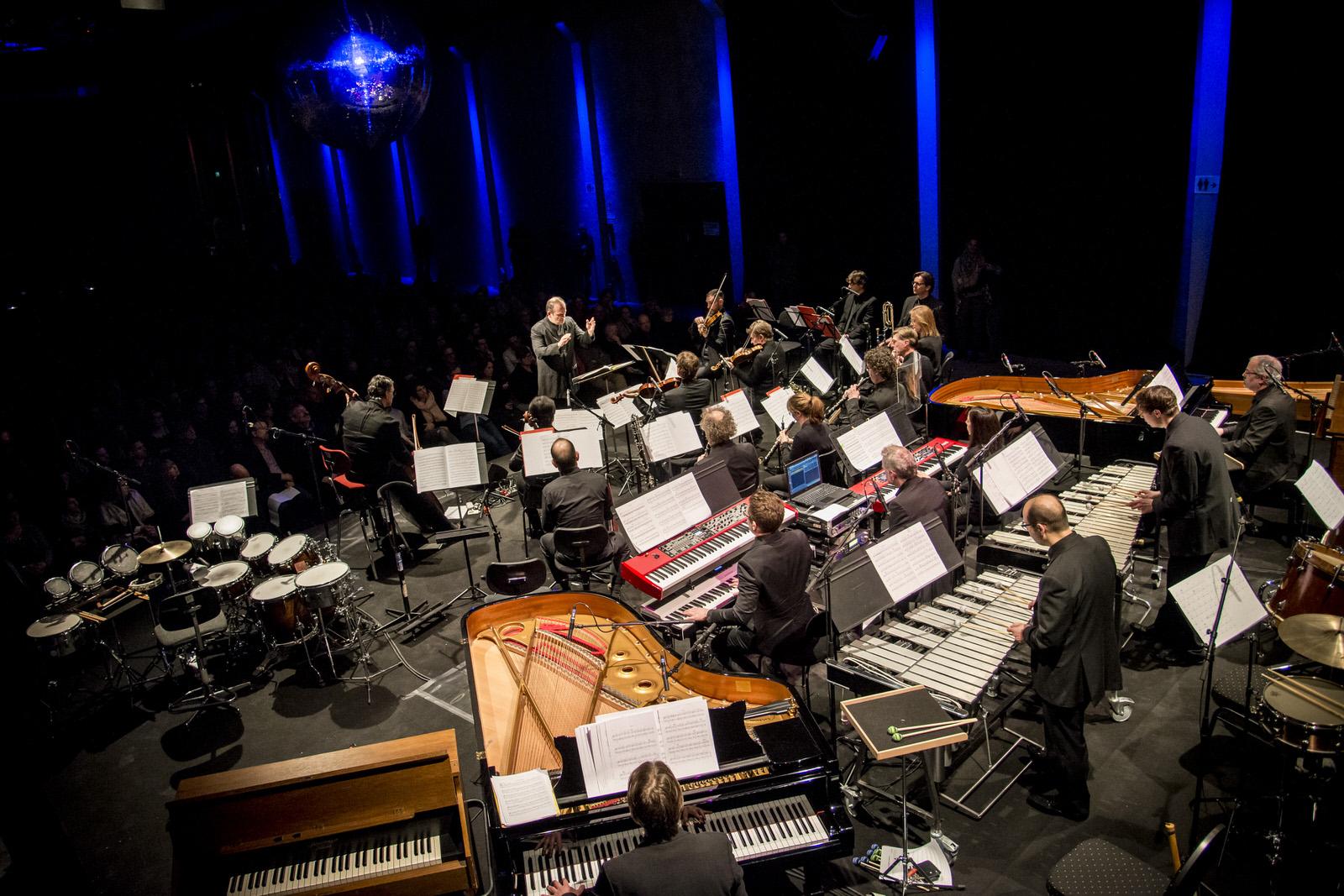 Beim Konzert spielte das Gürzenich-Orchester Stücke von Steve Reich und John Adams – Roth: »sehr urban musique« –, Ligeti – »viel abstrakter« – und Varèse – »Großvater der elektronischen Musik«. Dazwischen erschienen, auf einer erhöhten Galerie, Schmickler, Schwellenbach und Voigt hinter den Laptops.