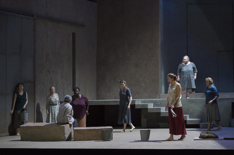 Das Bühnenbild von Richard Peduzzi ist schlicht gehalten, zeigt den Hinterhof mit einem großen Torbogen. Links der stets verschlossene Ausgang aus dem Haus.