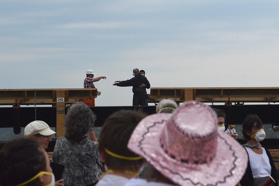 Ein RWE-Mitarbeiter wird von Besetzer*innen zum Tanz auf dem Braunkohleförderband aufgefordert. Dazu spielt das Orchester Schostakowitschs Walzer Nr. 2. Braunkohletagebau Hambach, August 2015