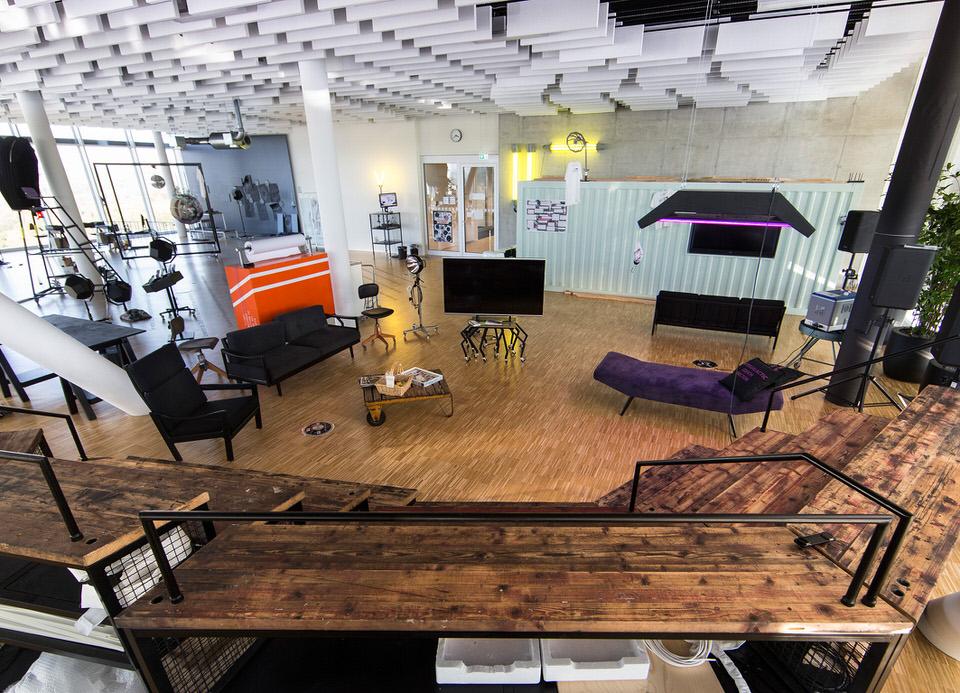 Die Platform 12: In der rechten Bildhälfte steht der »Intergalaktische Couchdoktor«, ein Ensemble aus einer lila Couch und einer darüber hängenden lila verkleideten Lampe • FotoBosch