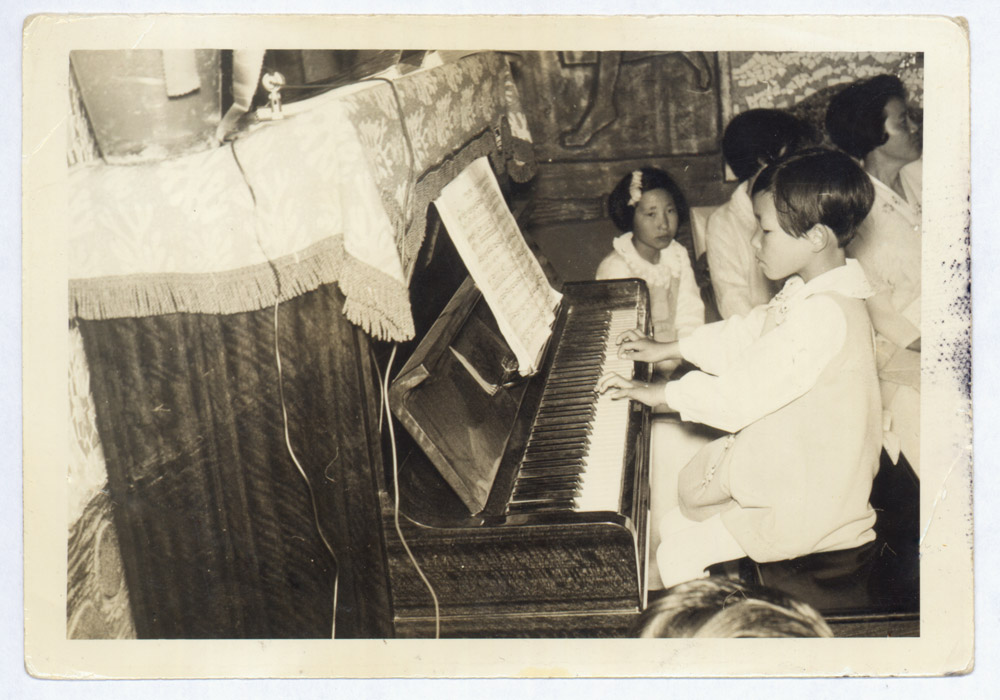 Kindheitsfoto von Unsuk Chin am Klavier. »Wenn ich Ablenkung brauche, übe ich stundenlang Klavier, das gibt viel mir Energie, weil ich mich da mit einem großartigen Repertoire beschäftigen kann, welches schon existiert. Ich wollte ja eigentlich Konzertpianistin werden, aber dafür hätte ich schon als Kind eine kontinuierliche Spezialausbildung bekommen müssen, und das ging nicht. Es gab kein Geld, in den 1960er und frühen 1970er Jahren war Südkorea eines der ärmsten Länder der Welt.«